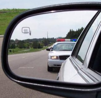 Police seen in the rear view mirror